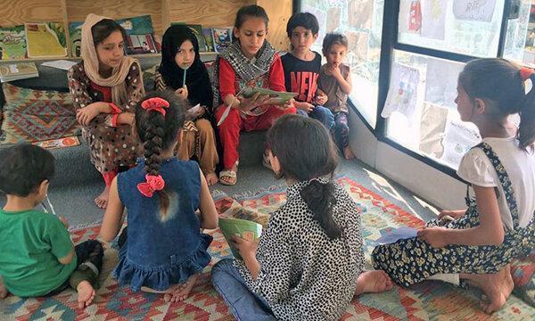 عکس ، کتاب خواندن بچه های افغان در اتوبوس